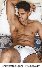 Good looking and very attractive and sexy male model with a modern and fashionable dark hairstyle and a trendy beard and big muscles and a gym fit body is posing on the bed in underwear or swimshorts