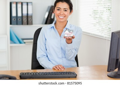 Good looking woman holding a miniature house while looking at the camera at the office