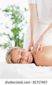 Good looking woman relaxing on a lounger during massage with closed eyes in a wellness center