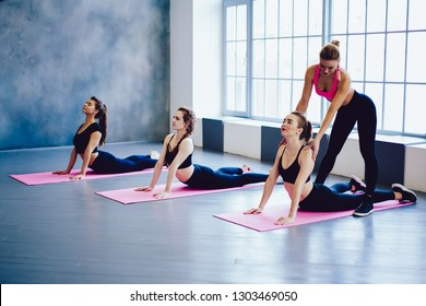 Good looking yoga instructor doing fitness stretching backbend exercise together teaching caucasian people at group training class in sport studio, healthy lifestyle wellness and motivation concept