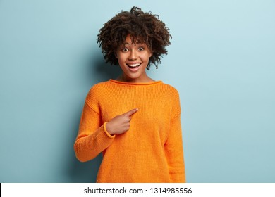 Good looking young African American woman with curly hairstyle, points at herself, wears orange jumper, asks something, has happy expression, isolated over blue background. Do you mean exactly me?