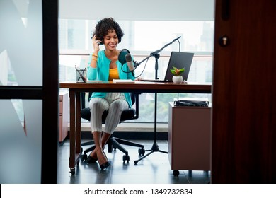 Good looking young black female making an online podcast recording for her online show. Attractive millennial African American business woman using headphones in front of microphone for radio program.