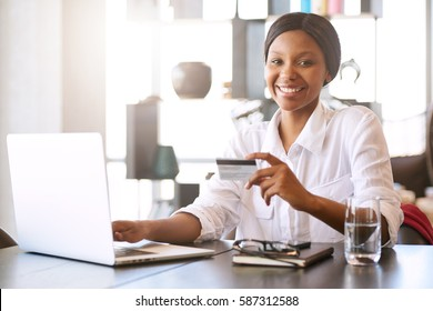 Good looking young black woman smiling at the camera while seated in front of her computer at her dining room table behind her notebook where she is making online payments with her credit card.