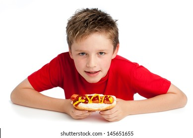 Good looking young boy eating a hotdog with tomato ketchup and mustard. Isolated on white background.