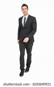 Good looking young business man in black suit full body isolate on white background with walking action