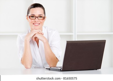 good looking young businesswoman sitting in office with laptop