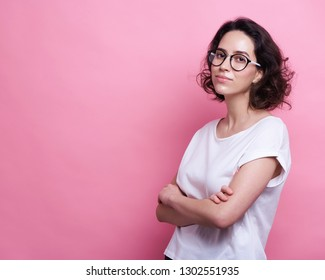Good looking young Caucasian woman in round transparent eyewear, keeps hand raised, dressed in casual outfit, pretends holding something wonderful, isolated over pink background.