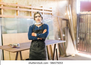 Good looking young confident woman working as carpenter in her own woodshop