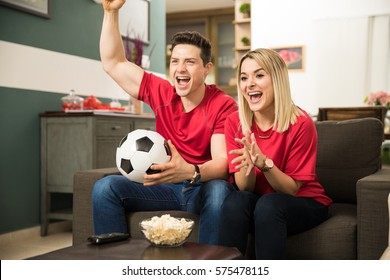 Good looking young couple looking surprised and excited while watching a soccer game at home