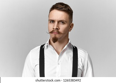 Good looking young groom with stylish neat haircut, hipster mustache and goatee beard posing isolated wearing smoothly ironed white shirt and black suspenders on wedding day, having serious look
