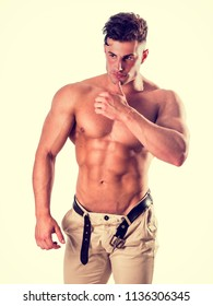 Good Looking Young Gym Fit Man Showing His Sexy Six Pack Abs While Looking To a Side. on Light Background in Studio