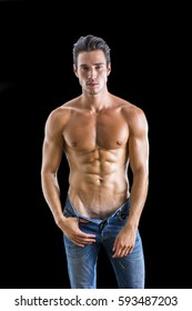 Good Looking Young Gym Fit Man Showing His Sexy Six Pack Abs While Looking at the Camera. No Underwear Under his Jeans, Isolated on Black Background.