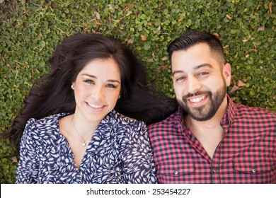 Good looking young Hispanic couple lying on the grass and relaxing in a park