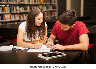 Good looking young Hispanic couple studying together in the library