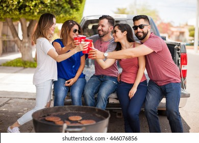 Good looking young Hispanic friends sitting next to a grill outdoors and making a toast with beer and plastic cups