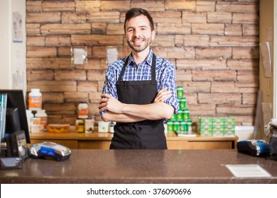 Good looking young male cashier standing at the checkout counter and greeting customers with a smile
