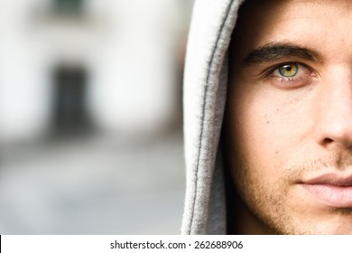 Good looking young man with blue eyes in the street wearing hooded jacket
