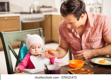 Good looking young man eating breakfast and feeding her baby girl at home