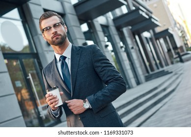 Good looking young man in full suit and glasses looking away and holding disposable cup while standing outdoors