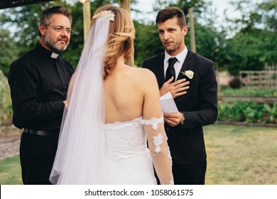 Good looking young man holding a paper and reading wedding vows for his bride. Traditional wedding ceremony rituals of a couple in park.