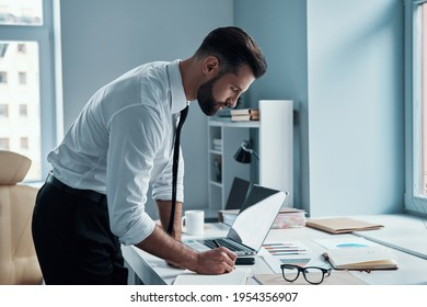 Good looking young man in shirt and tie working with documents in office - Shutterstock ID 1954356907