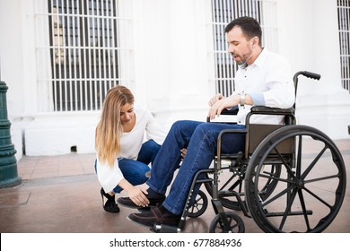Good looking young man in a wheelchair getting his legs in place with the help of his girlfriend