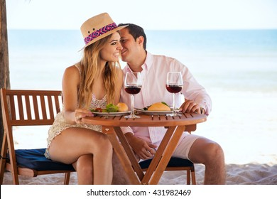 Good looking young man whispering and flirting with her girlfriend while they enjoy a meal at the beach