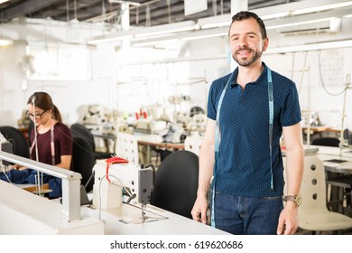 Good looking young man working as a tailor in a textile factory
