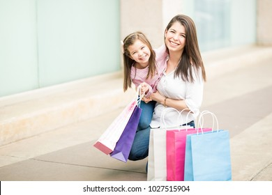 Good looking young mother and daughter with shopping bags outside a store in shopping center