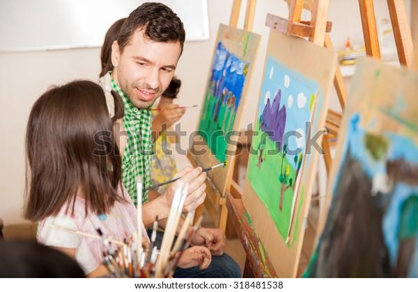 Joven profesor de buen aspecto trabajando en una pintura con uno de sus alumnos durante la clase de arte