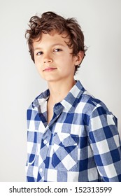 Good looking young teenager wearing a blue and white checked shirt, looking straight into the camera