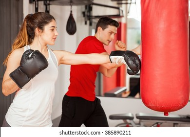 Good looking young woman with boxing gloves practicing on a punching bag next to her instructor