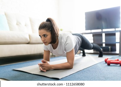 Good looking young woman doing a plank exercise at home