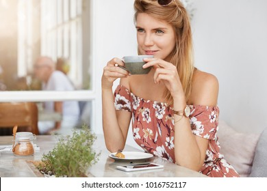 Good looking young woman with light hair, wears fashionable summer clothing, drinks hot tasty espresso or tea while waits for someone at cafe. Pretty female has coffee break after work at office