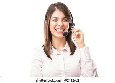 Good looking young woman wearing a headset and working in a call center with a smile