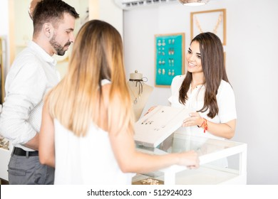 Good looking young woman working at a store selling some jewelry to a couple