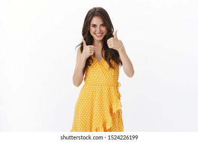 Good luck, keep going. Gorgeous supportive stylish woman agree, like picked outfit, show thumbs up and smiling pleased, agree excellent choice, accepting and judging nice taste, white background