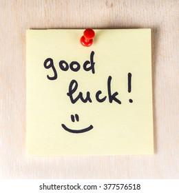 Good luck note on paper post it pinned to a wooden board