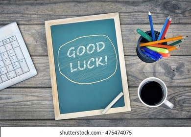 Good luck text on school board and coffee on desk