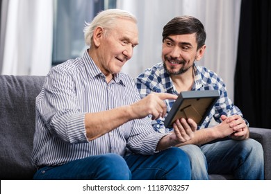 Good memory. Cheerful aged father and his son sitting on the sofa while holding a photo frame