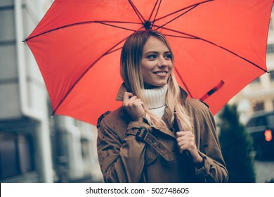 Good mood at any weather. Attractive young smiling woman carrying umbrella and adjusting her coat while walking by the street