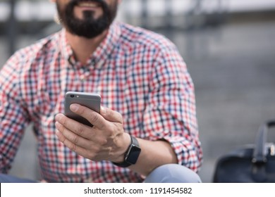 In good mood. Close up of a smartphone being used by a positive bearded man
