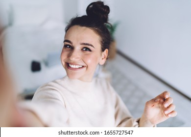 Good mood lady with expansive smile enjoying started weekends and taking selfie on mobile phone on blurred background