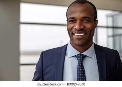 Good mood. Portrait of positive delighted young african businessman in suit is standing and looking at camera with wide smile