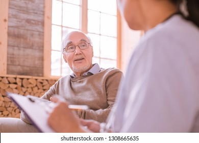 Good mood. Relaxed senior man sitting in cozy sofa while speaking with his doctor