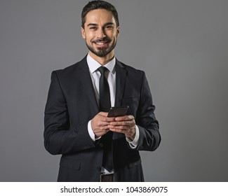 In a good mood. Waist up portrait of smiling amused cheerful businessman using a modern smartphone. Isolated on gray background