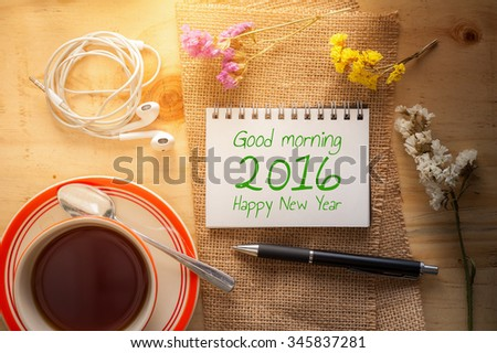 good morning 2016 happy new year is written on opened notepad with pen
