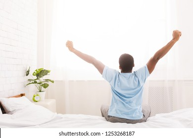 Good morning! African-american man waking up in bed and stretching his arms, back view, copy space
