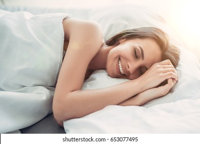 Good morning! Attractive young woman is lying on bed with her hands near face and smiling with closed eyes