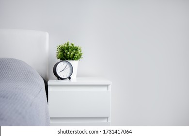 good morning concept - alarm clock and houseplant on bedside table and copy space over white wall background